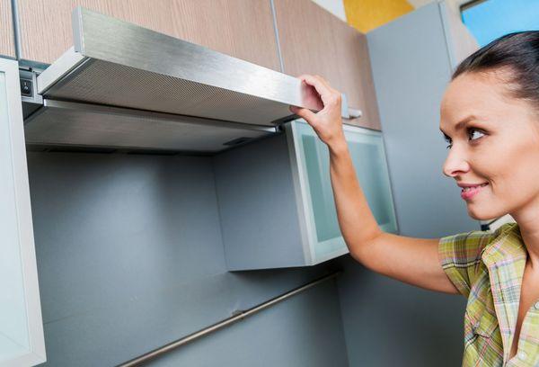 женщина стоит у вытяжки для кухни