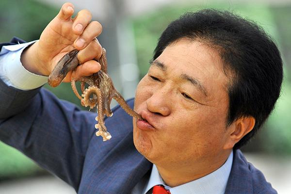 Мужчина ест живого осьминога