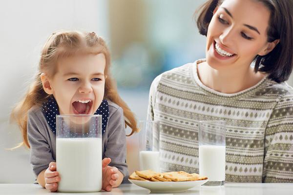 Мама с дочкой пьют молоко
