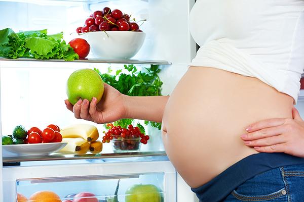 Беременная женщина у холодильника с фруктами и овощами
