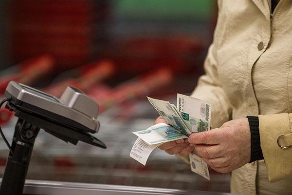 Женщина расплачивается в продуктовом магазине
